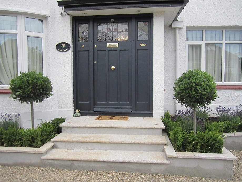 Front door framed with Bay laurels two lights in paving to uplight in dark