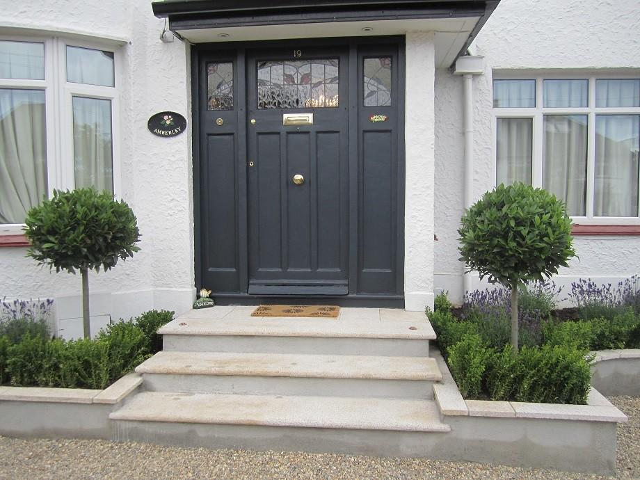 Front door framed with Bay laurels two lights in paving to uplight in dark