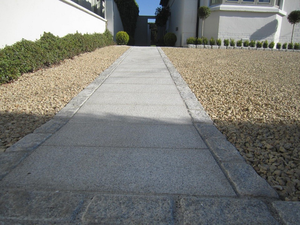 Path created using 600x300x30mm silver granite slabs bordered by tumbled silver granite cobbles