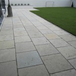 Limestone patio with silver granite cobble edge